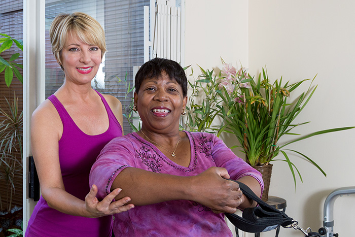 Patte James with injury rehabilitation client doing shoulder and chest exercises on the Reformer