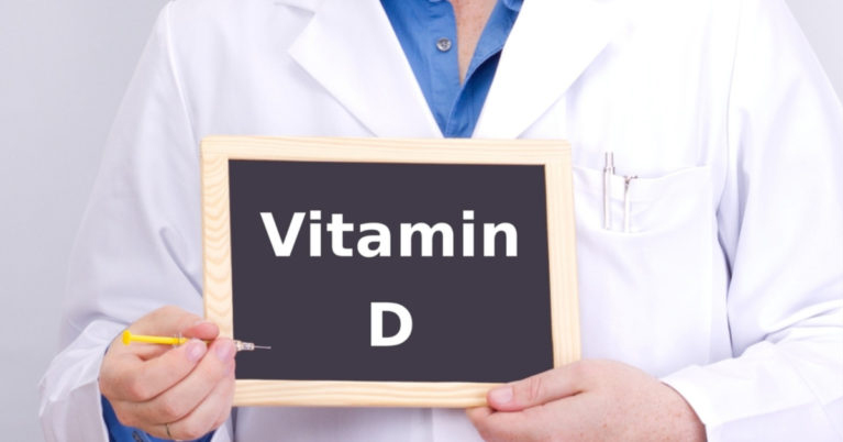 Person in lab coat holding Vitamin D sign
